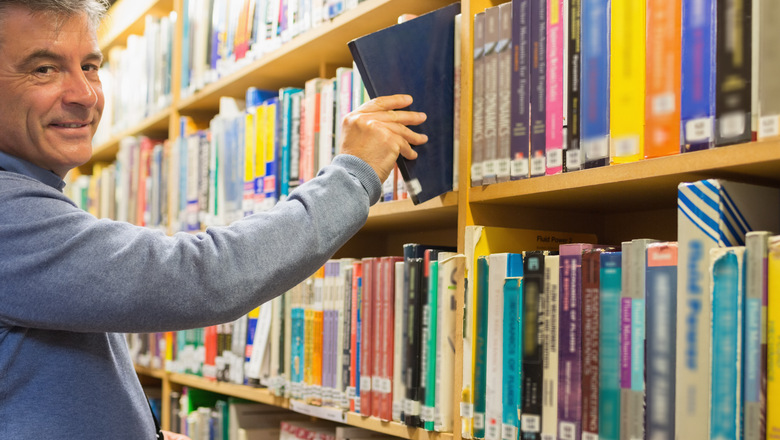 Smiling man taking a book from the shelves in library