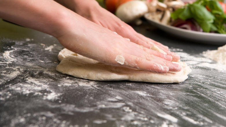 A pair of female hands prepare some bread dough on the counter for pizza.